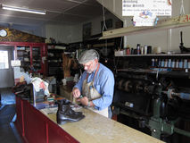 The Cobbler. A traditional shoe repair workshop with a craftsman worker and owner royalty free stock images