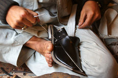 Cobbler. A Asian Cobbler stitching a traditional shoe near Peshawar Stock Image