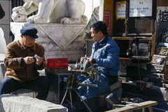 Cobbler and customer. The cobbler and the customer of the street, suide in shaanxi china shooting royalty free stock image