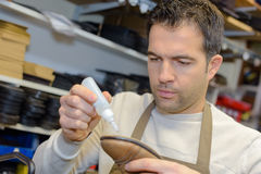 Cobbler gluing sole shoe. Cobbler gluing sole of shoe royalty free stock photo