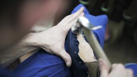 Cobbler hammering a blue boot sole stock video footage