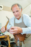Cobbler hammering sole boot Stock Images