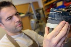 Cobbler holding deck shoe Stock Photography