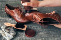 Cobbler holding shoe and applying shoe shiner. Cobbler holding brown shoe and applying shoe shiner on it royalty free stock photos