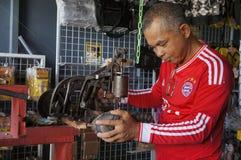 Cobbler. Maarop Bin Jusoh, 52, sewing shoes customers using traditional machine at his shop stock photos