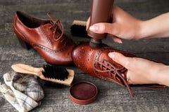 Cobbler polishing shoe with shoe shiner. Cobbler polishing brown shoe with shoe shiner royalty free stock image