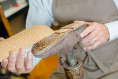 Cobbler restoring worn shoe. Cobbler stock photography