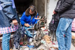 Cobbler in Rural China. In modern China, although the economy continues to develop, people still live a simple life in the countryside. Old clothes and shoes are stock image