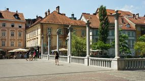 Ljubljana, Slovenia - 07/19/2015 - The Cobbler`s Bridge with Corinthian and Ionic pillars as lamp-bearers in old town, sunny day royalty free stock photography