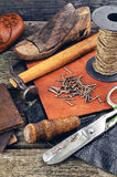 Cobbler's tools on a wooden background. Cobbler's tools and old shoes royalty free stock photos