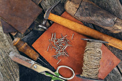 Cobbler's tools on a wooden background. Cobbler's tools and old shoes stock image