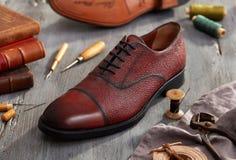 Cobbler`s workshop closeup. Men leather shoes on wood royalty free stock photos