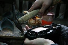 Cobbler. Shoemaker tools. Shoemaker workshop. Shoemaker sews shoes royalty free stock images