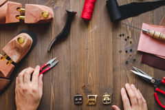 Cobbler with tools work process dark background top view. With hands royalty free stock photography