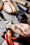 Cobbler tools in workshop dark background close up. Cobbler tools in workshop on dark background close up with hands royalty free stock photo