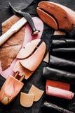 Cobbler tools in workshop dark background top view close up. Cobbler tools in workshop on dark background top view close up royalty free stock photography