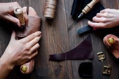Cobbler tools in workshop dark background top view. Cobbler tools in workshop on dark background top view with hands stock images
