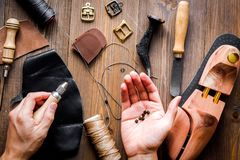 Cobbler tools in workshop dark background top view. Cobbler tools in workshop on dark background top view with hands stock photography