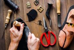 Cobbler tools in workshop dark background top view. Cobbler tools in workshop on dark background top view with hands stock photos