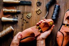 Cobbler tools in workshop dark background top view. Cobbler tools in workshop on dark background top view with hands stock image