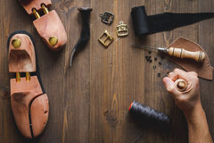Cobbler tools in workshop dark background top view. Cobbler tools in workshop on dark background top view with hands stock images