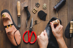 Cobbler tools in workshop dark background top view. Cobbler tools in workshop on dark background top view with hands stock photos