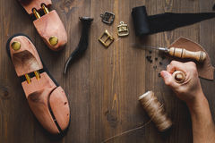 Cobbler tools in workshop dark background top view. Cobbler tools in workshop on dark background top view with hands royalty free stock photo