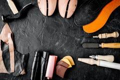 Cobbler tools in workshop dark background top view mock up. Cobbler tools in workshop on dark background top view mock up stock photo