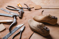 Cobbler tools in workshop on the wooden table . Cobbler tools in a workshop on the wooden table stock photography