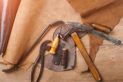 Cobbler tools in workshop on the wooden table . Top view. Cobbler tools in workshop on a wooden table . Top view stock photography