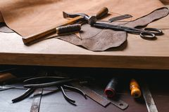 Cobbler tools in workshop on the wooden table . Top view. Cobbler tools in workshop on a wooden table . Top view royalty free stock images