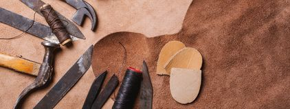 Cobbler tools in workshop on the wooden table . Top view. Cobbler tools in workshop on wooden table . Top view stock photo