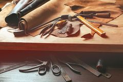 Cobbler tools in workshop on the wooden table . Top view. Cobbler tools in workshop on a wooden table . Top view royalty free stock photo