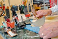 Cobbler using half round knife. Bench stock photos