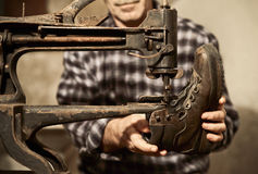 Cobbler at work. With sewing machine stock image