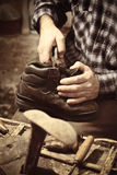 Cobbler at work. With old tools royalty free stock image