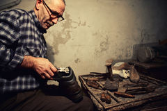 Cobbler at work. With old tools stock photography