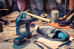 Cobbler workplace with tools, leather and shoes Royalty Free Stock Photo