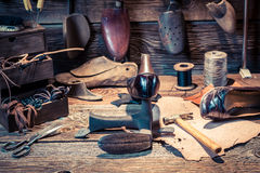 Cobbler workplace with tools, shoes and laces Royalty Free Stock Images