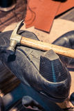 Cobbler workplace with tools, shoes and leather Royalty Free Stock Images