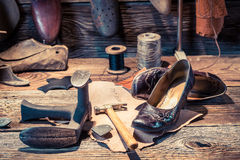 Cobbler workshop with tools, leather and shoes Stock Photo
