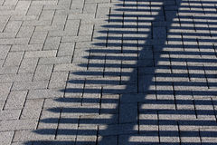 Cobbles and the shadow of the fence Stock Image