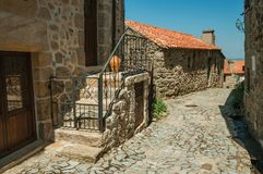 Cobblestone alley on slope and stone old houses. Facade of old house and stone staircase with iron railing on cobblestone alley at Linhares da Beira. A medieval stock photo