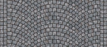 Road curved cobblestone texture 006. Cobblestone arched pavement road with edge courses at the sidewalk. Seamless tileable repeating 3D rendering texture Royalty Free Stock Photo