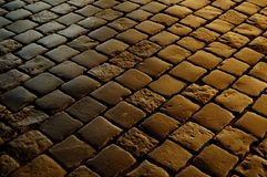 Cobblestone background. European medieval cobblestone pedestrian narrow street in the night lights Royalty Free Stock Images