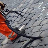 Cobblestone crack repair. A workman repairing cracks in a cobblestone road or street Royalty Free Stock Photo