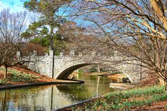 Cobblestone Foot Bridge Over A Waterway. An Arched Cobblestone foot bridge traveling across a flowing stream of water Royalty Free Stock Photos