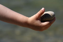 Cobblestone held in child right hand. On the beach royalty free stock images