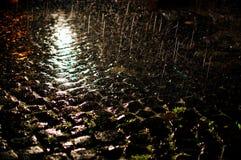Cobblestone hit by rain at night stock photo
