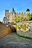 Cobblestone lane through the fortress of Carcassonne, France. Historic fortress of Carcassonne behind arched cobblestone lane, France Royalty Free Stock Images